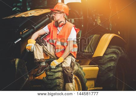 Bulldozer Construction Worker Resting on His Heavy Duty Machinery.