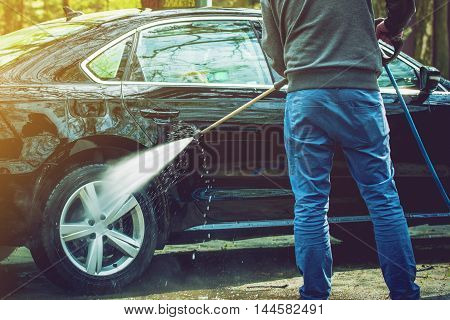 Men Cleaning His Modern Car. Outdoor Car Washing by High Pressured Water