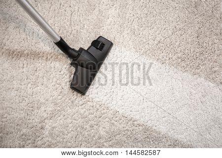 Vacuum cleaner vacuuming dusty carpet