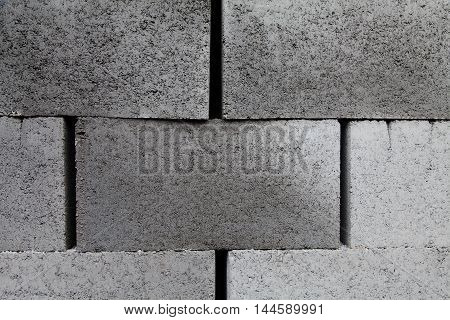 Gray building cinder blocks made of cement stacked close-up background. Lot of large concrete bricks stacking texture