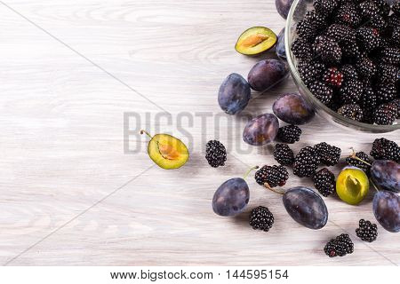 ripe plums and blackberries on wooden background. from above. Left space for text