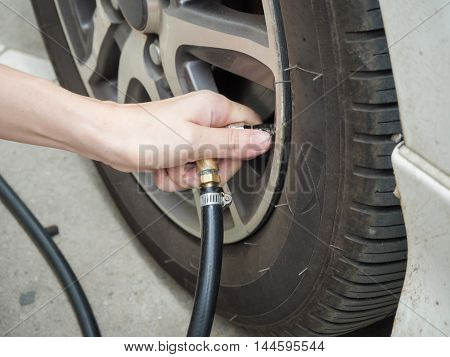 Closeup man checking air pressure and filling air in the tire