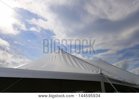 white entertainment tent tops against a dramatic sky