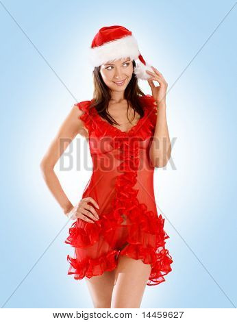 Young sexy Santa sitting on a big present over blue background