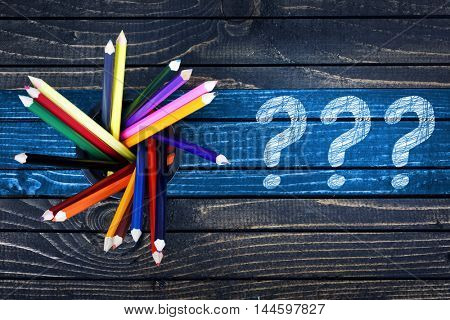 Question marks painted and group of pencils on wooden table
