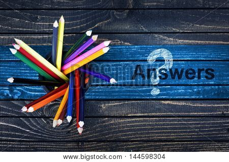 Answers text painted and group of pencils on wooden table