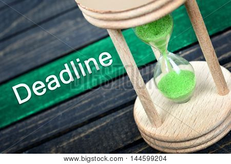 Deadline text and hourglass on wooden table