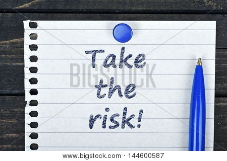 Take the risk text on page and pen on wooden table