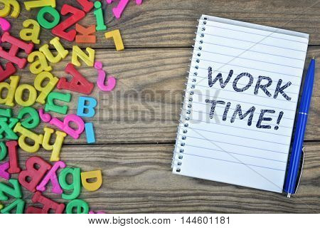 Work time text on notepad and magnetic letters on wooden table
