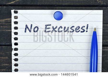 No excuses text on page and pen on wooden table