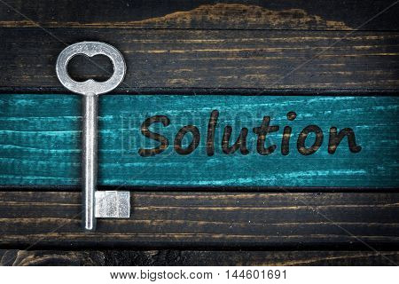Solution word and old key on wooden table