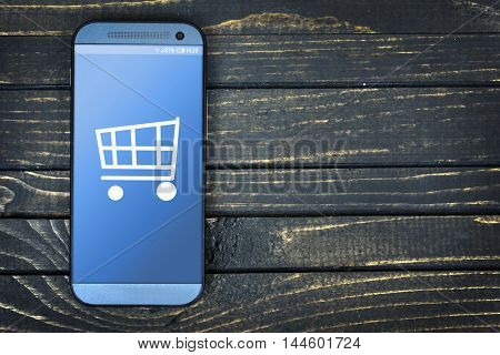 Shopping Cart on phone screen over wooden table