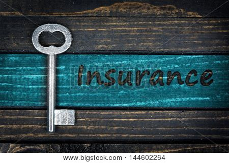 Insurance word and old key on wooden table