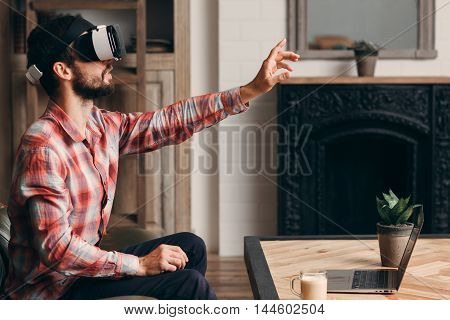 Man using virtual reality headset. Young guy touching invisible screen in vr glasses. Modern technology, innovation, cyberspace, entertainment concept