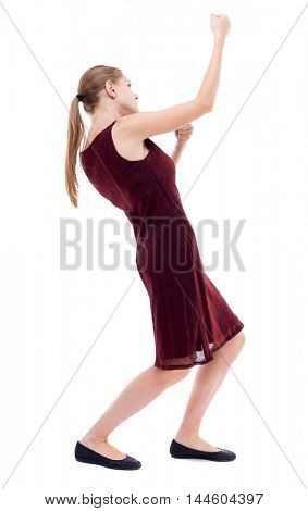 back view of standing girl pulling a rope from the top or cling to something. Isolated over white background. A girl in a burgundy dress pulls the load