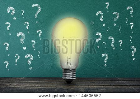 Question text on green board and light bulb on table