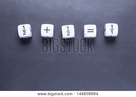 white fraction mah number dices showing simple equation half plus half equal whole on blackboard good for background and teaching blogs room for copyspace