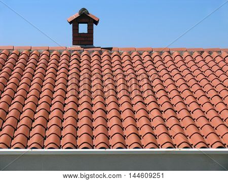 Brick chimney on sky background house with tiled roof.