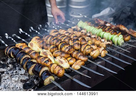 Grilled vegetables barbecue skewers vegetarian dinner picnic food shish kebab with roasted pepper, potatoes, champignon, on coal ember brazier. Concept of lifestyle rustic street food preparation