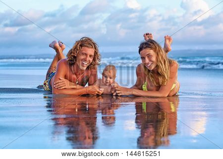Happy family travel - father mother baby son walk with fun along sunset sea surf on black sand beach. Active parents lifestyle people outdoor activity on tropical island summer vacation with child.