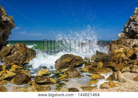 seashore with rocks and splashing waves with spray