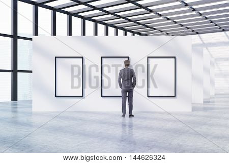 Man looking at pictures at museum exhibition. Concrete floor white walls panoramic windows glass roof. Concept of art appreciation. 3d rendering. Mock up