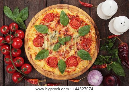 Italian spaghetti pizza margherita with cheese, chery tomato and basil