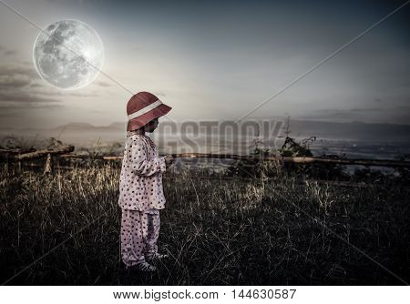 Asian child relaxing outdoors with bright full moon at night travel on vacation. Adorable girl in night sky under beautiful full moon. Vintage tone effect. Low key style. The moon were NOT furnished by NASA.