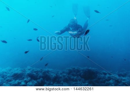 Underwater image of diver young man snorkeling and free diving among fishes