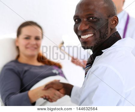 Black Male Doctor Shake Hands As Hello With Female Patient