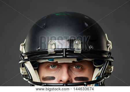 Isolated on black background closeup of head of blue-eyed man with eye black wearing football helmet and looking at camera prepared to face a challenge.
