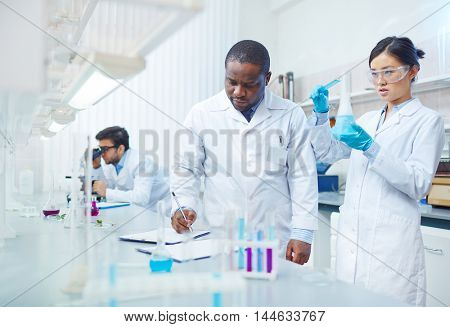 Focused female Asian scientist pouring blue liquid into flask as male African-American laboratory scientist writing down results. Latin-American colleague looking into microscope in background.