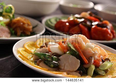 Sauteed scallops with lemon mushroom and carrot on white dish
