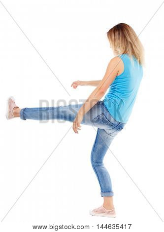 back view of woman funny fights waving his arms and legs. Isolated over white background. The blonde in a blue shirt and jeans, raised her leg.