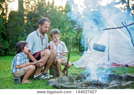 Father and two sons camping in the forest summertime cooking potatoes