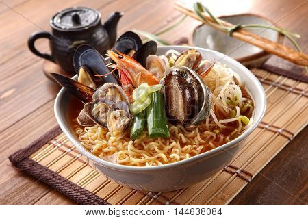 Big bowl of instant noodle with abalone shrimp clams onion and sprout on wooden korean table
