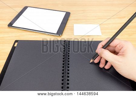 Hand Holding Pencil Writing On Blank Black Book With Table And Business Card On Wooden Table, Mock U