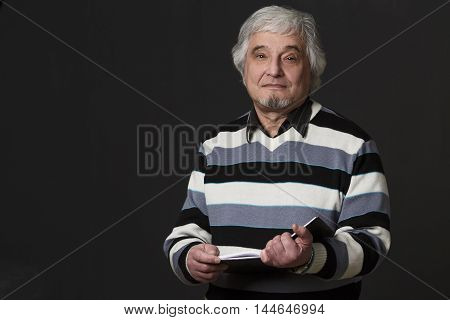 Portrait of professor man of university or colleage holding book or notebook in front of him and looking at camera isolated on black background in studio.