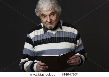 Image of handsome professor man of university or colleage looking at camera while holding notebook or book in front of him isolated on black in studio.