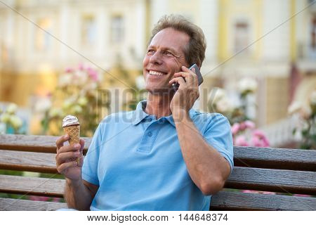 Mature man with phone smiling. Guy holding ice cream. Good mood and vacation. Sounds pretty funny.