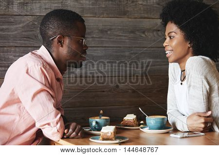 Happy Dark-skinned Couple Having Nice Conversation After Long Breakup, Looking At Each Other With Am