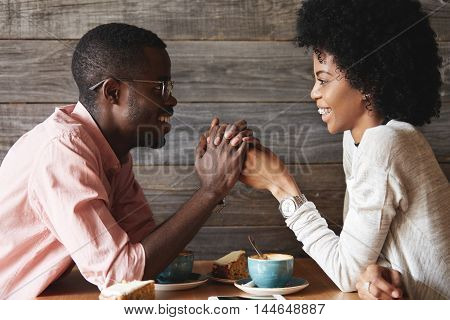 Dark-skinned Young Couple Sitting At Restaurant: Black Man In Glasses Holding His Girlfriend's Hands