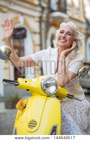 Mature lady waves hand. Lady on scooter is smiling. Meet old friends on vacation. Feeling at ease.