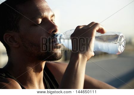 African American Man Drinking Cold Water With Eyes Closed. Young Dark-skinned Guy Enjoying His Bever
