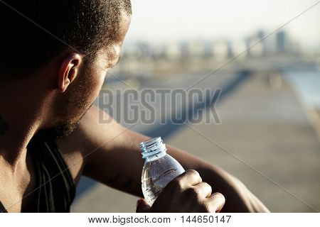 Young Muscular Build Man Drinking Water Of Bottle After Running, Looking Away, Sitting On Embankment