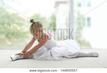 Cute ballerina sitting on the floor at ballet class