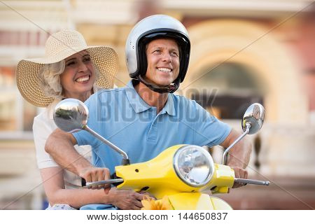 Mature couple on scooter smiles. Guy in a helmet. Hear the roar of motor. We are unstoppable.