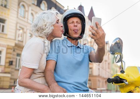 Mature couple showing tongues. Woman and man with phone. Memorable moment from our trip. No need to be shy.