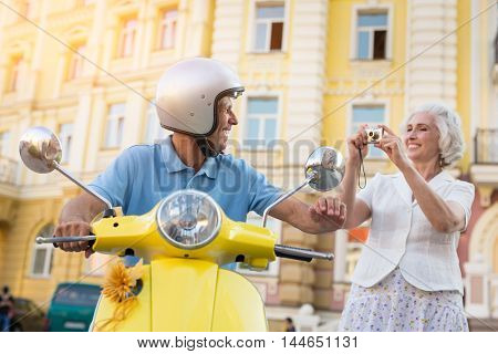 Woman smiling and holding camera. Mature couple on street background. Video from our vacation. Filming in high definition.