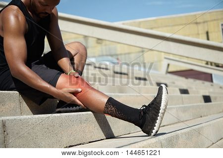 Young Sportsman With Strong Athletic Legs Holding Knee After Suffering Ligament Injury During Runnin